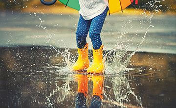 Girl splashing in a puddle with yellow wellies.