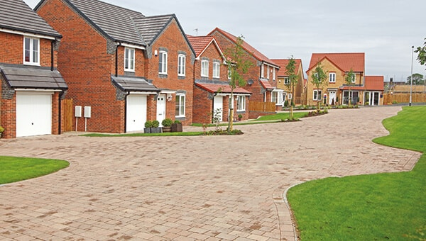 A row of new houses, with brick driveways.