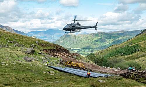 Helicopter delivering HDPE to Hydro Scheme in air
