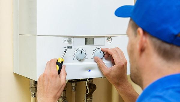 Person servicing a boiler.