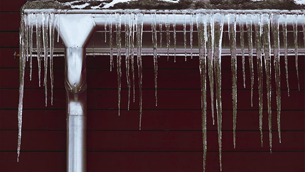 Icicles hanging from a black gutter.