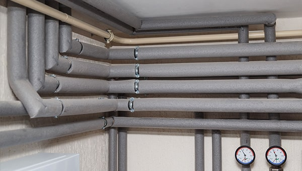 Pipes in a corner insulated with foam lagging.