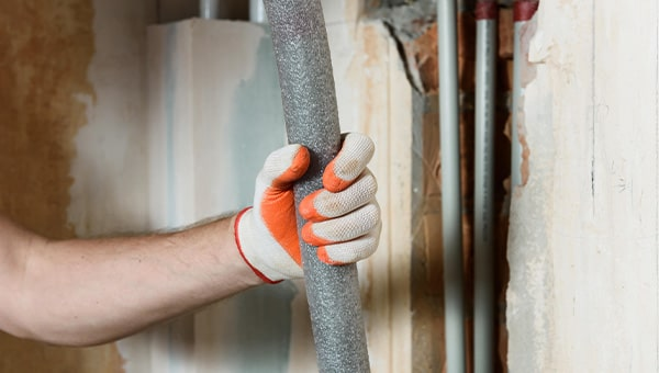 Person with gloves holding grey foam pipe lagging.