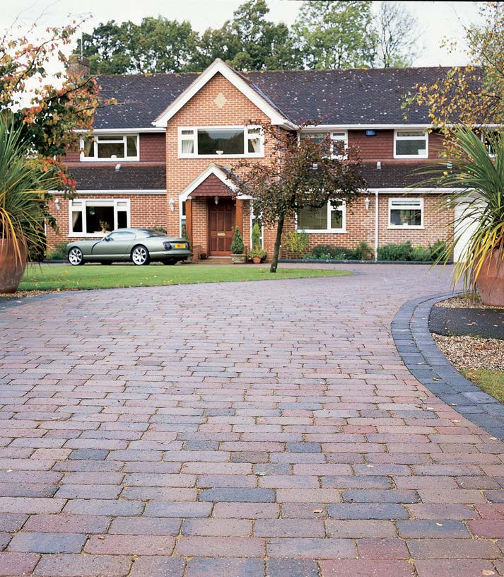 House with a brick-laid driveway.